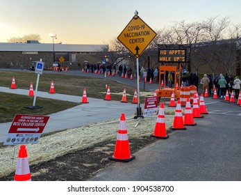 Gloucester, New Jersey, USA, 1-28-2021: Covid-19 vaccination center sign outdoors with people waiting in the line