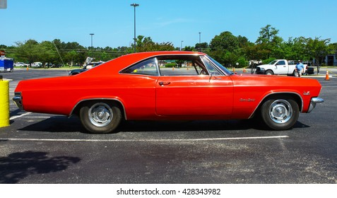 GLOUCESTER, VA - MAY 28, 2016: A red 1965 Chevrolet Impala SS 396 at the First Aaron's rental car and Motorcycle show, the show is Sponsored by Aaron's furniture rental of Gloucester