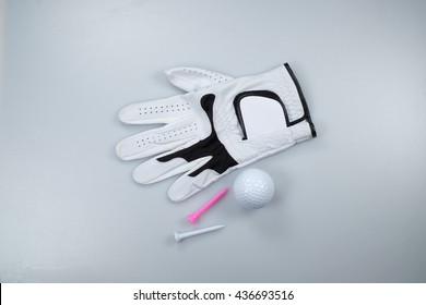 Glove, golf ball and tees isolated on white