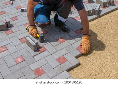 A gloved craftsman lays down the paving stones in layers. Laying gray concrete paving slabs in the courtyard of the house on a sandy foundation.
