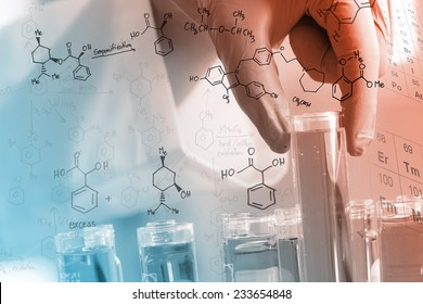 Gloved hand holding the test tubes, with chemical equations background,  in the laboratory
