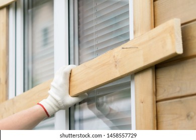 gloved hand holds a board in front of a window to protect windows from natural disasters