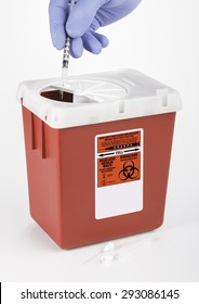 A gloved hand inserting Medical and/or Dental waste into a medium size Sharps container. White background.