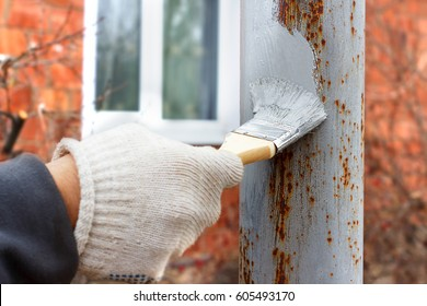 Gloved hand painting primer anti rust on steel poles for construction. Half - painted surface. Smear of paint brush.