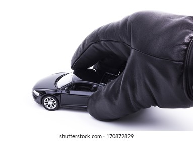A gloved hand is picking up a sports car