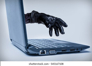 A gloved hand reaching out through a laptop, signifying a cybercrime or Internet theft while using Internet media.