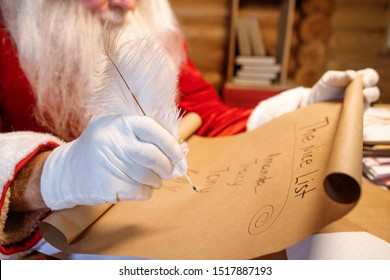 Gloved hand of Santa holding white plume over nice list on unrolled paper while getting ready for Christmas
