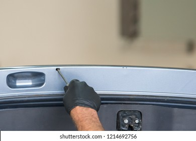 A gloved hand spraying rust proofing into a small hole in the hatch of a vehicle.