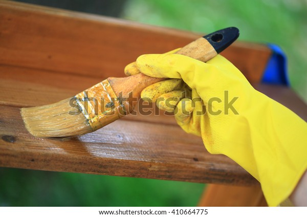 Gloved hand varnishing plank outdoor