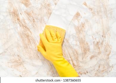 Handgeliebte, die eine schmutzige Marmortheke oder einen schmutzigen Marmorboden mit Schwamm abwischen
