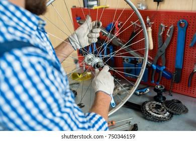 Gloved hands of bike repairman fixing central cog of wheel