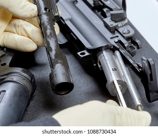 Gloved hands changing the caliber on an AR15 rifle after cleaning it