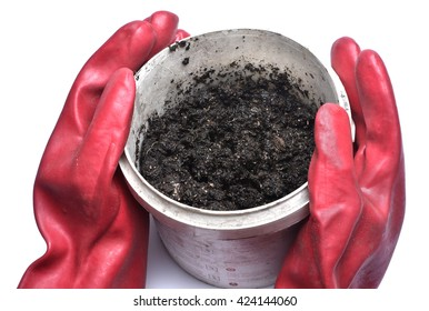 Gloved hands hold contaminated soil on white background