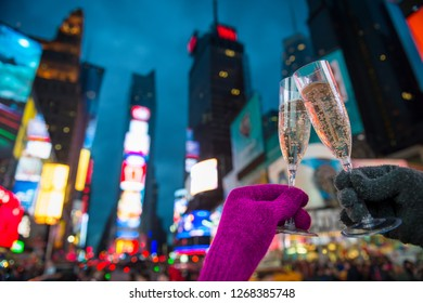 Gloved hands holding up Champagne glasses in a Mew Year's Eve toast against the bright lights of Times Square, New York City