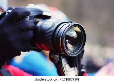 A gloved person holding a camera