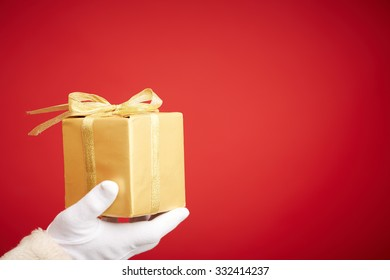 Gloved Santa hand holding giftbox wrapped into golden paper