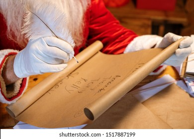 Gloved Santa holding pen over big paper with list of kids names while looking through it by table