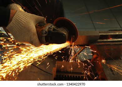 a gloved worker with a grinder cuts a carbide plate and this causes a lot of sparks