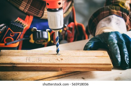 Gloved worker working with an electric drill
