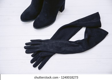Gloves and autumn boots made of genuine black suede leather on a white wooden background