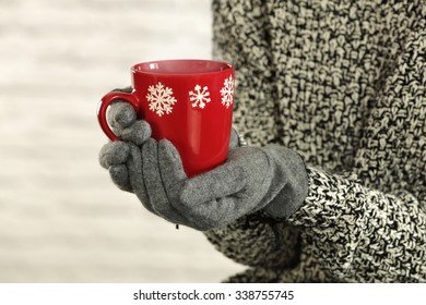 gloves of gray color and red mug space