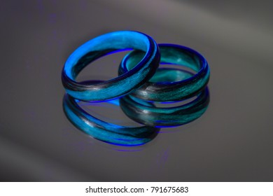 Glow in the dark carbon fiber wedding rings on a mirror