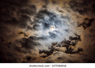 The glow of a full moon dramatically lights clouds in a night sky.