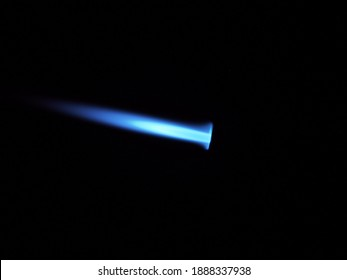 The glow of a gas lighter torch in the dark. Close-up.