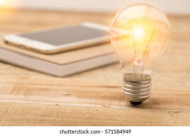 glow light bulb and smart phone on wooden background