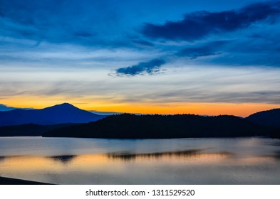 Glow of sun setting behind the Adirondack Mountains reflected on Lake Placid in Upstate New York.