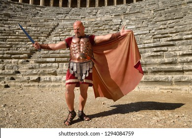 Glowering Roman Gladiator with sword spreading cape in sun on stage at the ancient Aspendos theatre Aspendos, Antalya, Turkey - November 8, 2012