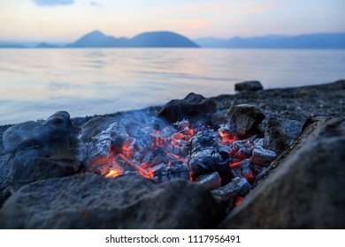 Glowing ashes smoldering in a stone fire ring on the shore of Lake Koya in Hokkaido, Japan