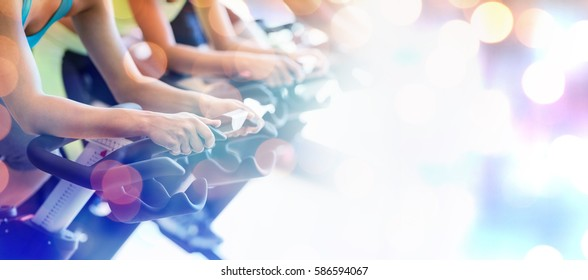 Glowing background against cropped image of people in spin class