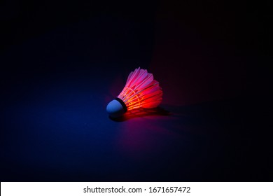 Glowing badminton shuttlecocks on a black background
