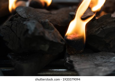 Glowing barbecue charcoal briquettes in a BBQ coal lighter. Fire flame is started using fire starters placed among charcoal in the barbeque charcoal grill.