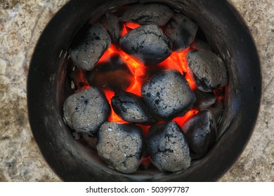 Glowing barbecue charcoal briquettes in a BBQ coal lighter.