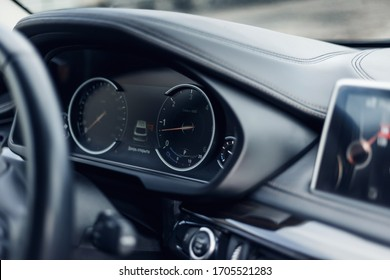 Glowing beautiful dashboard of a modern expensive car. The interior of the car. The foreground is blurred. Modern car interior details. Car detailing. Selective focus