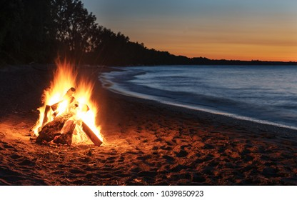 Glowing Bonfire on the Beach at Sunset