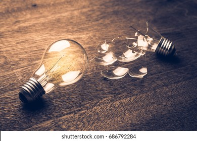 Glowing and broken light bulb comparison concept, problem and solution, failure and success, learning from mistake
