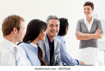 Glowing businesswoman presenting to her team in a meeting