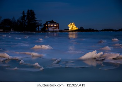 glowing Christmas lights on a tree near a house on the shore of an icy lake. night landscape with ice floes closeup and a city in the distance. selective focus.  blurred background. Cope space for you