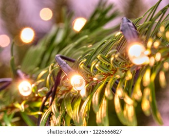 Glowing Christmas lights. Christmas tree decorated with garlands. Close-up