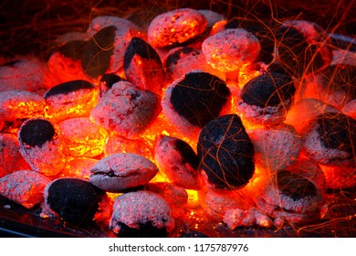 Glowing coal inside of a barbecue grill.