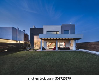 Glowing country house in a modern style with the large lawn. In front of the house there is a covered terrace with a lounge zone and a furnace. On the lawn there is a tree and flowerbeds. Outside.