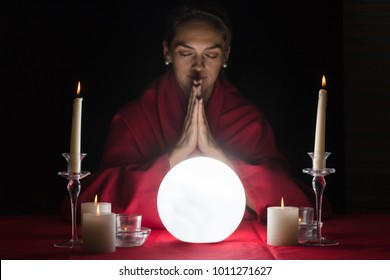 Glowing Crystal Ball In Front Of Woman Fortuneteller With Clasped Hands