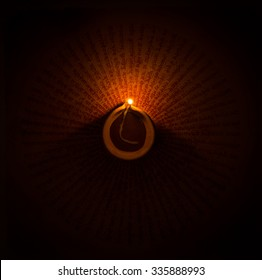 A glowing earthen ghee lamp in the dark. Handwritten mantra visible at the background.