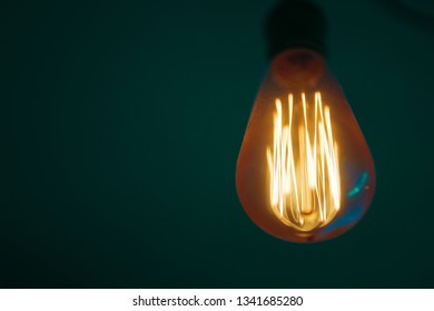 Glowing Edison lamp on green background