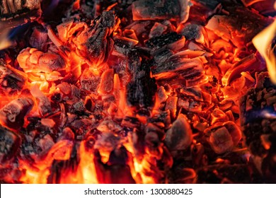 Glowing embers in hot red color, abstract background. The hot embers of burning wood log fire. Firewood burning on grill. Texture fire bonfire embers.