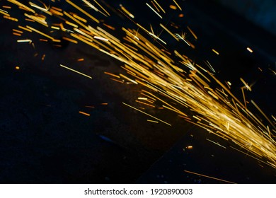 Glowing flow of steel metal welding spark dust particles shine in the sparkly dark background
