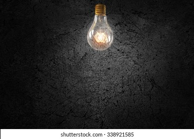 Glowing glass light bulb on concrete background